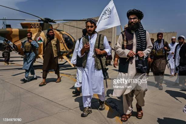 Anas Haqqani, center right, gets a tour of the military vehicles seized by Taliban fighters after the militant group seized the Hamid Karzai...