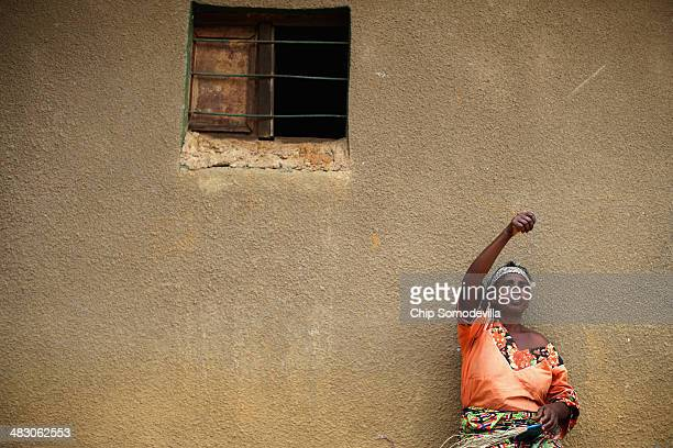 Anasitasia Nyirabashyitsi weaves a grass and thread bowl outside her home in a genocide reconciliation village April 6 2014 in Mybo Rwanda Before...
