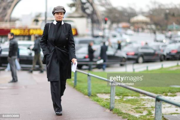 Anastasia Barbieri wears a gray beret hat a black coat with white collar black flared pants and black leather shoes outside the Hermes show during...