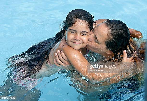 Anastasia Perez receives a kiss from her mother Shirley Perez as they cool off together at North Hollywood Pool in North Hollywood on June 24 2013