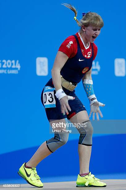 Anastasiia Petrova of Russia reacts in the Women's 58kg Weightlifting on day three of the Nanjing 2014 Summer Youth Olympic Games at Nanjing...