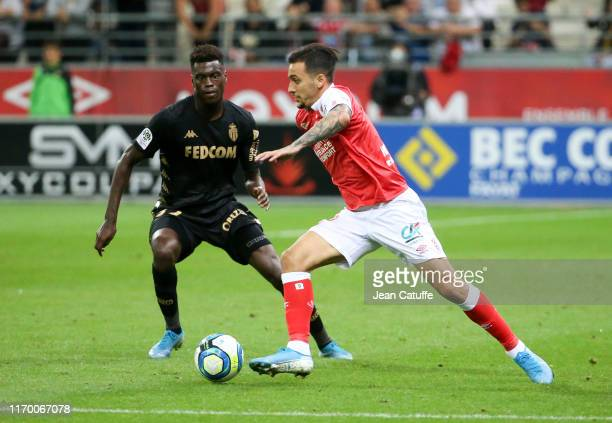 Anastasios Donis of Reims, Benoit Badiashile of Monaco during the Ligue 1 match between Stade de Reims and AS Monaco at Stade Auguste Delaune on...