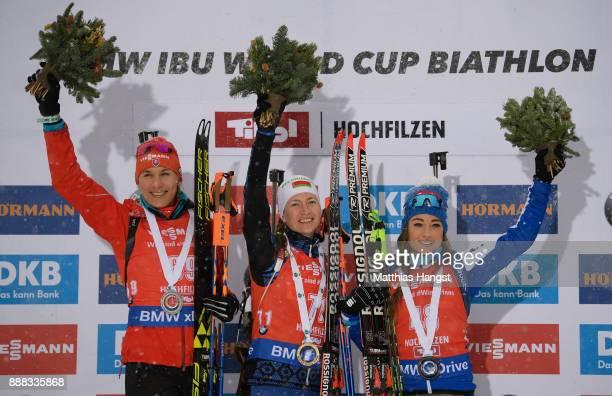 Anastasiya Kuzmina of Slovakia celebrates second place Darya Domracheva of Belarus celebrates first place and Dorothea Wierer of Italy celebrates...