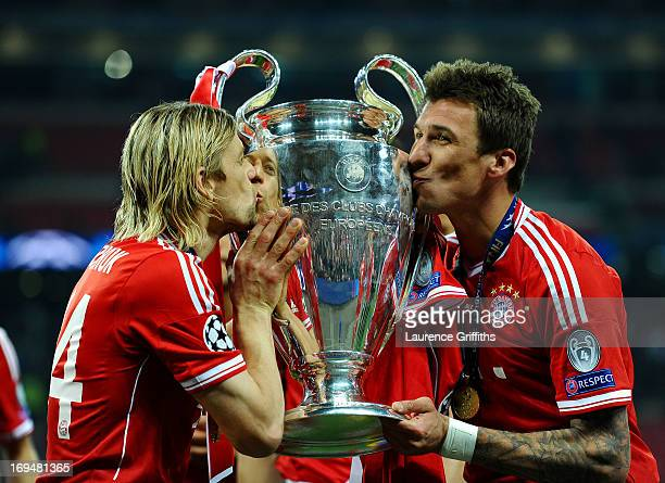Anatoliy Tymoshchuk of Bayern Muenchen and teammate Mario Mandzukic kiss the trophy after winning the UEFA Champions League final match against...