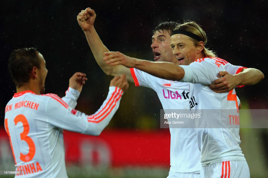 Anatoliy Tymoshchuk of Muenchen celebrates his team's second goal with team mates Thomas Mueller and Rafinha (R-L) during the Bundesliga match between SC Freiburg and FC Bayern Muenchen at MAGE SOLAR Stadium on November 28, 2012 in Freiburg im Breisgau, Germany.