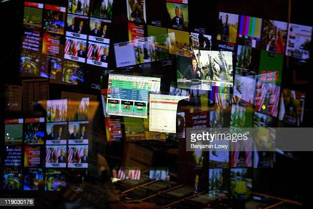 Anchor Adrian Finighan and several different live feeds are projected and reflected in the high tech broadcast center at the Al Jazeera English news...