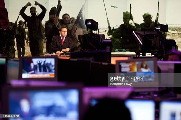 Anchor Adrian Finighan presents the news during a live broadcast of Al Jazeera English on March 22 2011 in Doha Qatar