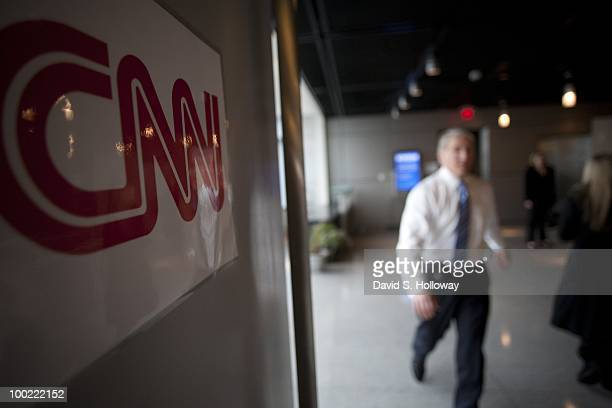 Anchor John King walks past a CNN logo sign on the set of his sunday morning political show 'State of the Union' briadcast from on top of the Newseum...