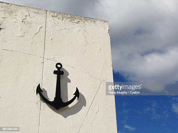 Anchor On White Wall Against Sky