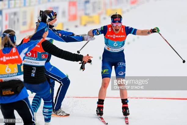Anchor woman Finland's Krista Parmakoski and team mates celebrate placing third in the women's 4x5 km relay race at the FIS Nordic Ski World...