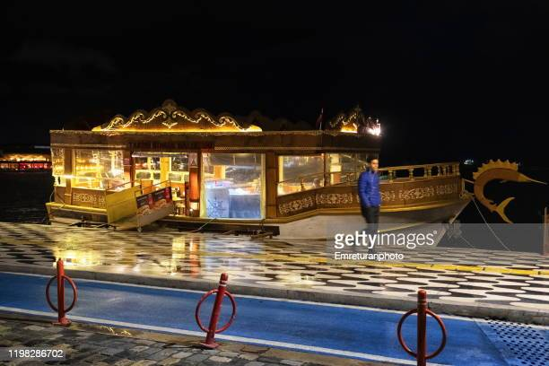 anchored boat restaurant along promenade at night,izmir. - emreturanphoto stock-fotos und bilder