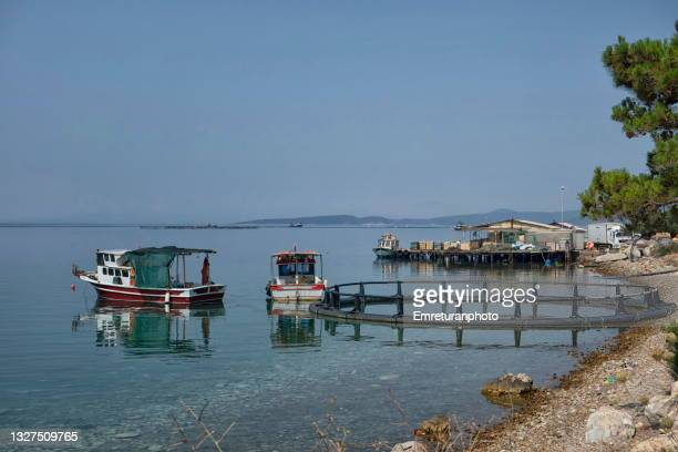 anchored boats and a fishing cage on the coast in karaburun. - emreturanphoto stock pictures, royalty-free photos & images