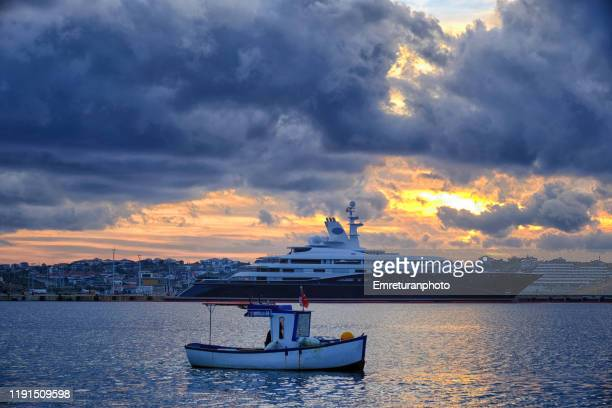 anchored boats and cloudy dramatic sky at cesme bay at sunset. - emreturanphoto stock pictures, royalty-free photos & images