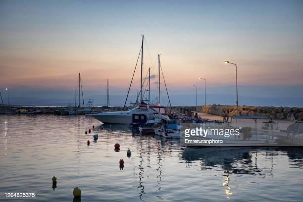 anchored boats at ciftlikkoy marina at sunset , aegean turkey. - emreturanphoto stockfoto's en -beelden