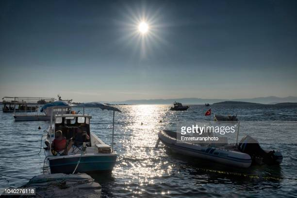 anchored boats at ildir bay on a sunny day. - emreturanphoto stock pictures, royalty-free photos & images