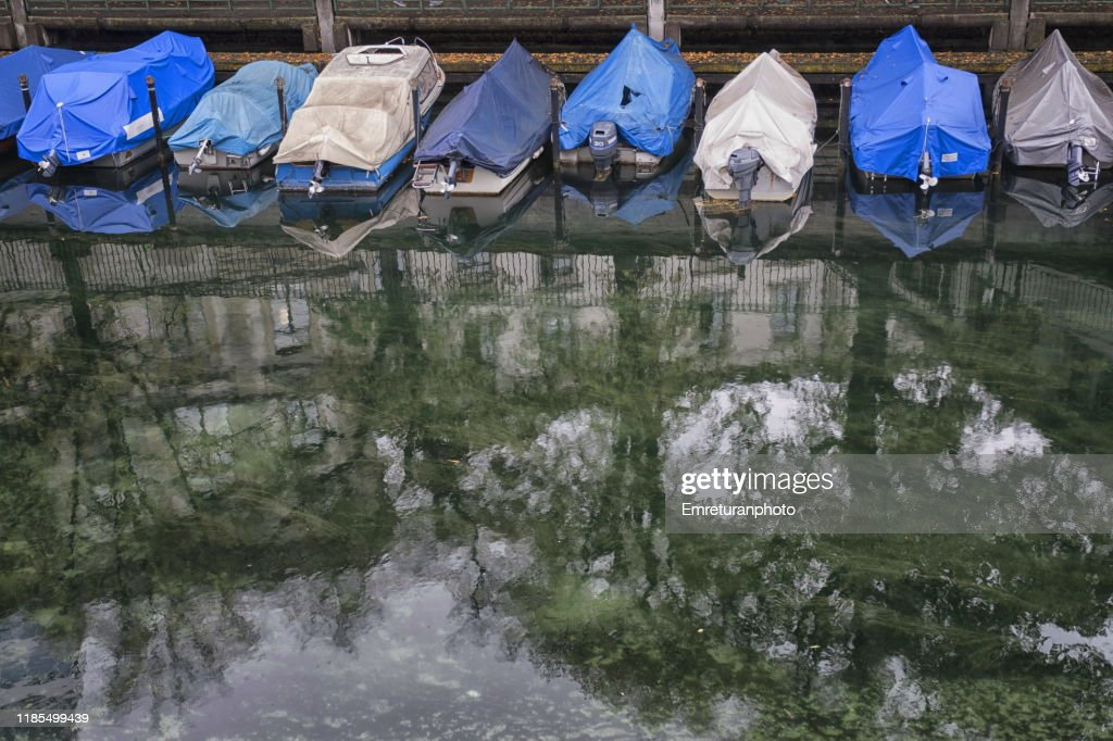 Anchored boats covered with nylon covers  along the river,Zurich. : Stock Photo