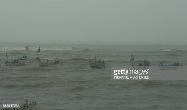 Anchored fishing boats are seen bobbing in the rough sea off a popular beachfront promenade in Mumbai on December 5 2017 Cyclone Ockhi brought heavy...