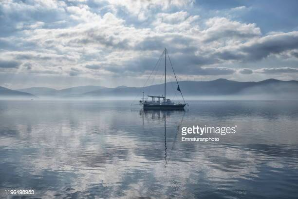 anchored sailboat on a tranquil cloudy day in the aegean sea. - emreturanphoto stock pictures, royalty-free photos & images