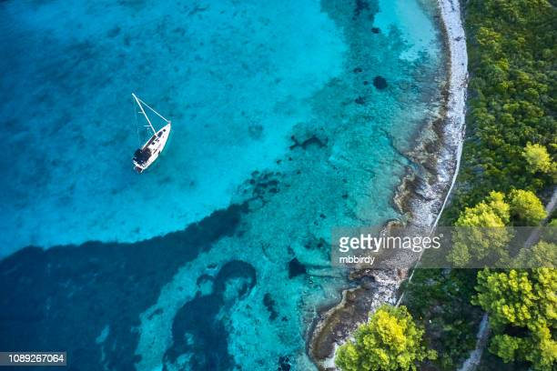 anchored sailboat, view from drone - coastline stock pictures, royalty-free photos & images