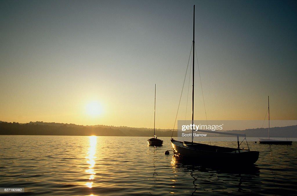 Anchored sailboats on a lake at sunset : Stock-Foto