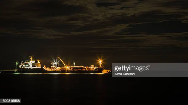 anchored ship at night - alma danison stock photos and pictures