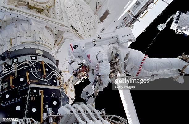 Anchored To A Restraint Device On The End Of The Remote Manipulator System Robot Arm Astronaut Michael LopezAlegria Uses A Pistol Grip Tool October...