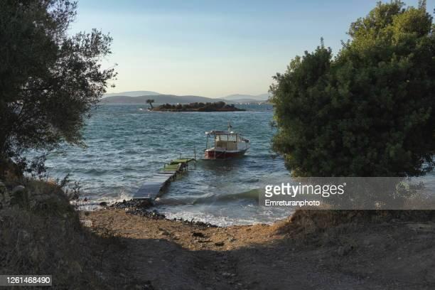 anchored wooden boat and small island at ildir bay. - emreturanphoto stock-fotos und bilder