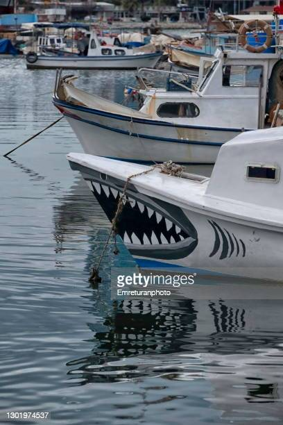 anchored wooden boat with shark jaws painting at inciralti marina,izmir.. - emreturanphoto stock pictures, royalty-free photos & images
