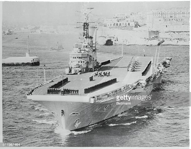 Its crew formed on deck the British aircraft carrier HMS Centaur slips past the picturesque shoreline of Malta leaving Grand Harbor for flying...
