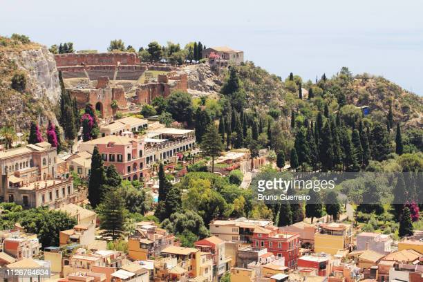 ancient amphitheater perching on hill against sea (teatro antico di taormina) - メッシーナ ストックフォトと画像