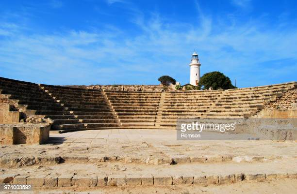 ancient amphitheater with lighthouse in background, paphos archaeological park, cyprus - パフォス考古学公園 ストックフォトと画像