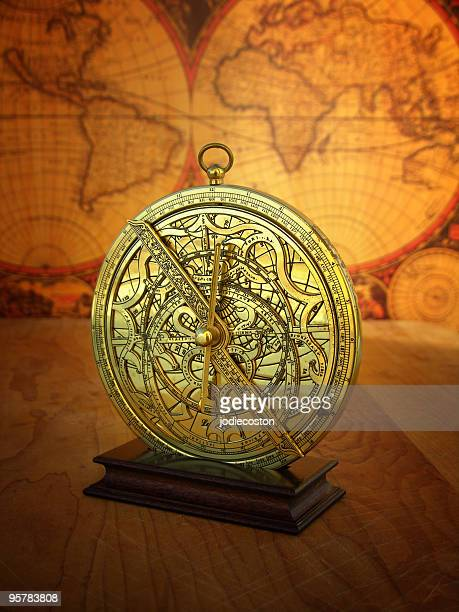 Ancient astrolabe in front of a vintage-style world map