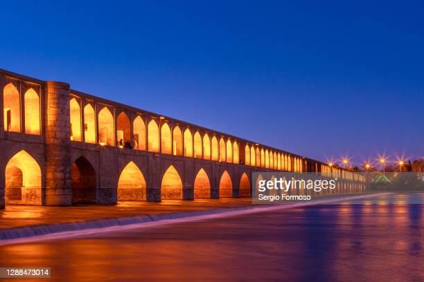 ancient bridge over a river. si-o-se pol, isfahan, iran - ザーヤンド川 ストックフォトと画像