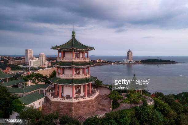 ancient chinese architecture with new qingdao china skyline by night - qingdao stock pictures, royalty-free photos & images