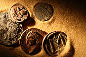 Ancient coins laying in golden sand