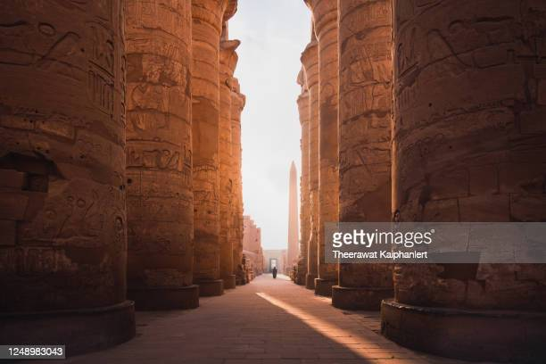 ancient corridor and columns of karnak temple complex in luxor city egpyt during sunrise - egypt stock pictures, royalty-free photos & images
