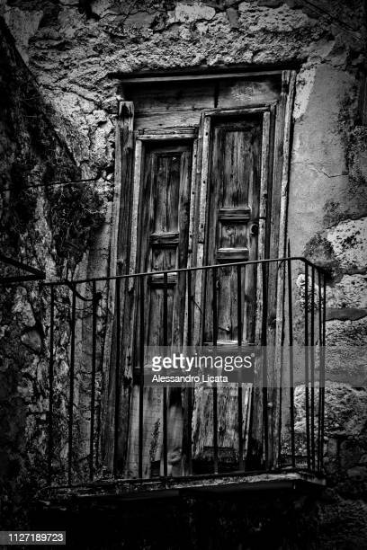 ancient crooked window - muro stock photos and pictures