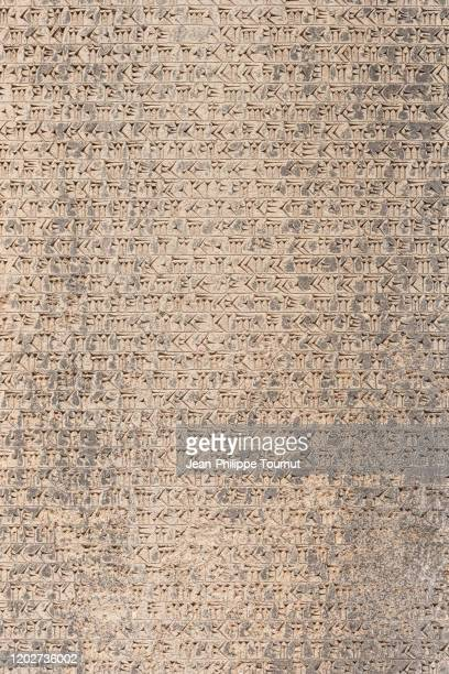 ancient cuneiform script of behistun inscription (bisotun), a multiligual message from darius the great, dating from the 5th century bc, zagros mountains, kermanshah province, iran - foot bone stock pictures, royalty-free photos & images