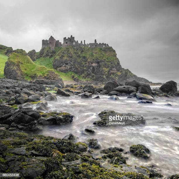 ancient dunluce castle on a cliff, ireland - castle stock photos and pictures