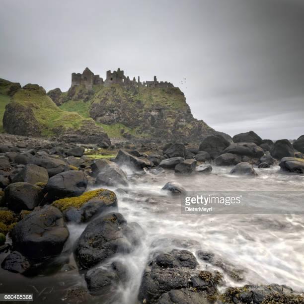 ancient dunluce castle on a cliff, ireland - dunluce castle stock photos and pictures