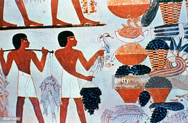 Ancient Egyptian wall paintings in a tomb at Thebes Egypt Men carrying food an abundance of fish wildfowl and what appears to be bunches of grapes