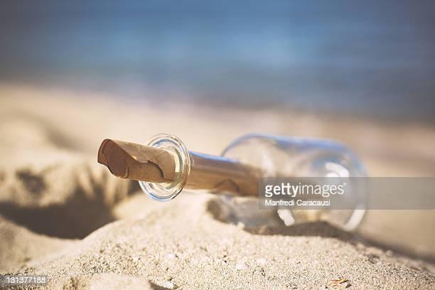 Ancient letter in glass bottle fallen on beach