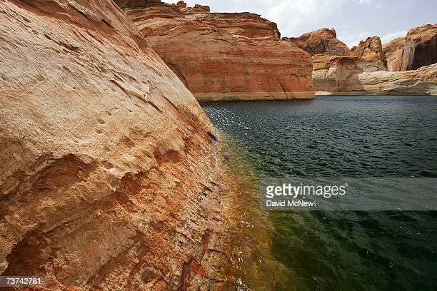 Ancient Moki or Anasazi people steps carved into huge steep rocks faces rise from deep under Lake Powell in Fiftymile Creek Canyon and up through the...