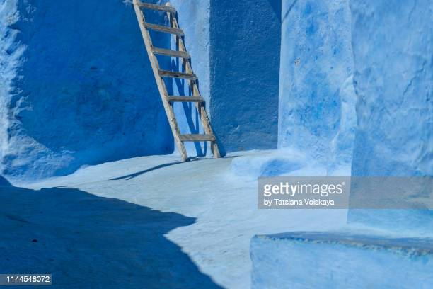 ancient painted wall with wooden handmade ladder, sunlight and shadow silhouette in narrow street of blue city - chefchaouen photos et images de collection