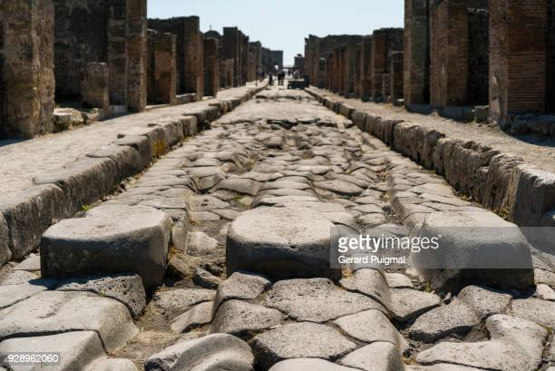 ancient pedestrian crossing and wheel ruts in the old roman city of pompeii (pompei, campania, italy). - pompeii stock photos and pictures