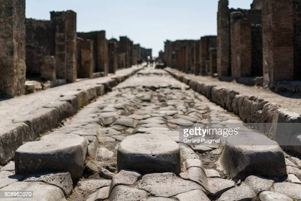 ancient pedestrian crossing and wheel ruts in the old roman city of pompeii (pompei, campania, italy). - pompeya fotografías e imágenes de stock