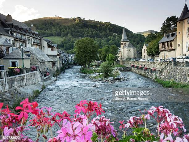 Ancient people in the Pyrenees of France that it crosses a great river, with an ancient bridge and a church.  France ,  Pyrenees, (Arreau)