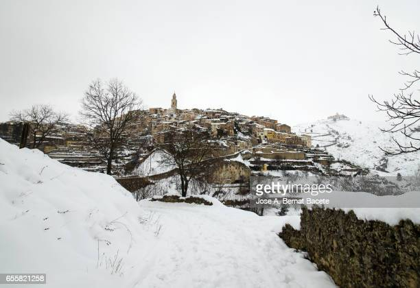 Ancient people of medieval construction snowed in winter, placed on a hill with a bridge of access