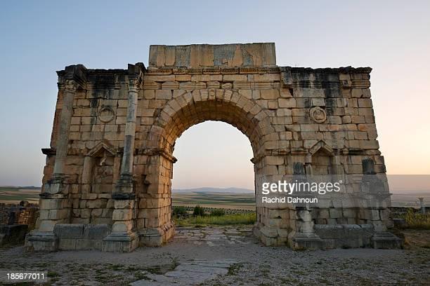 ancient roman ruins at sunset at the partially excavated roman city of volubilis near meknes, morocco. - volubilis fotografías e imágenes de stock
