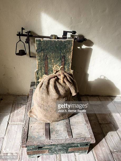 ancient rural big scale, to weigh the crops of the field in sacks of burlap - sac stock pictures, royalty-free photos & images